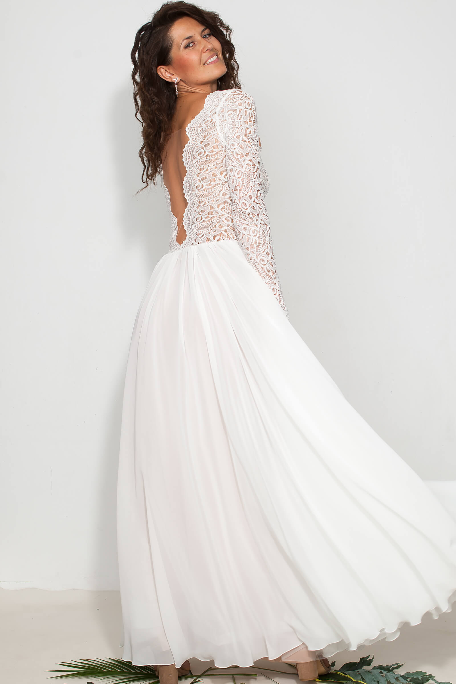 Skromna sukienka ślubna z szyfonem i głebokim dekoltem na plecach.