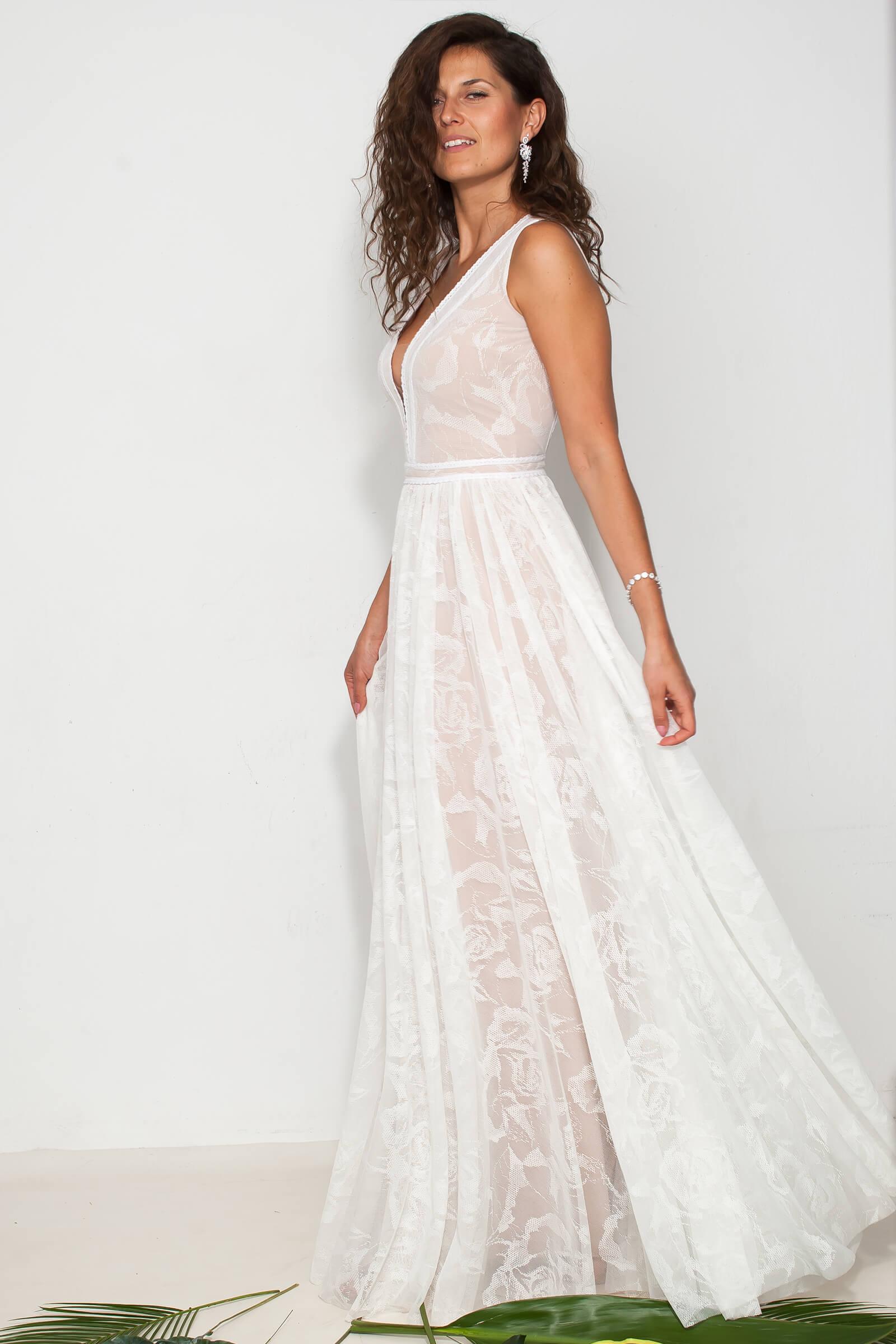Zabudowana skromna suknia ślubna z koronki w kwiaty.