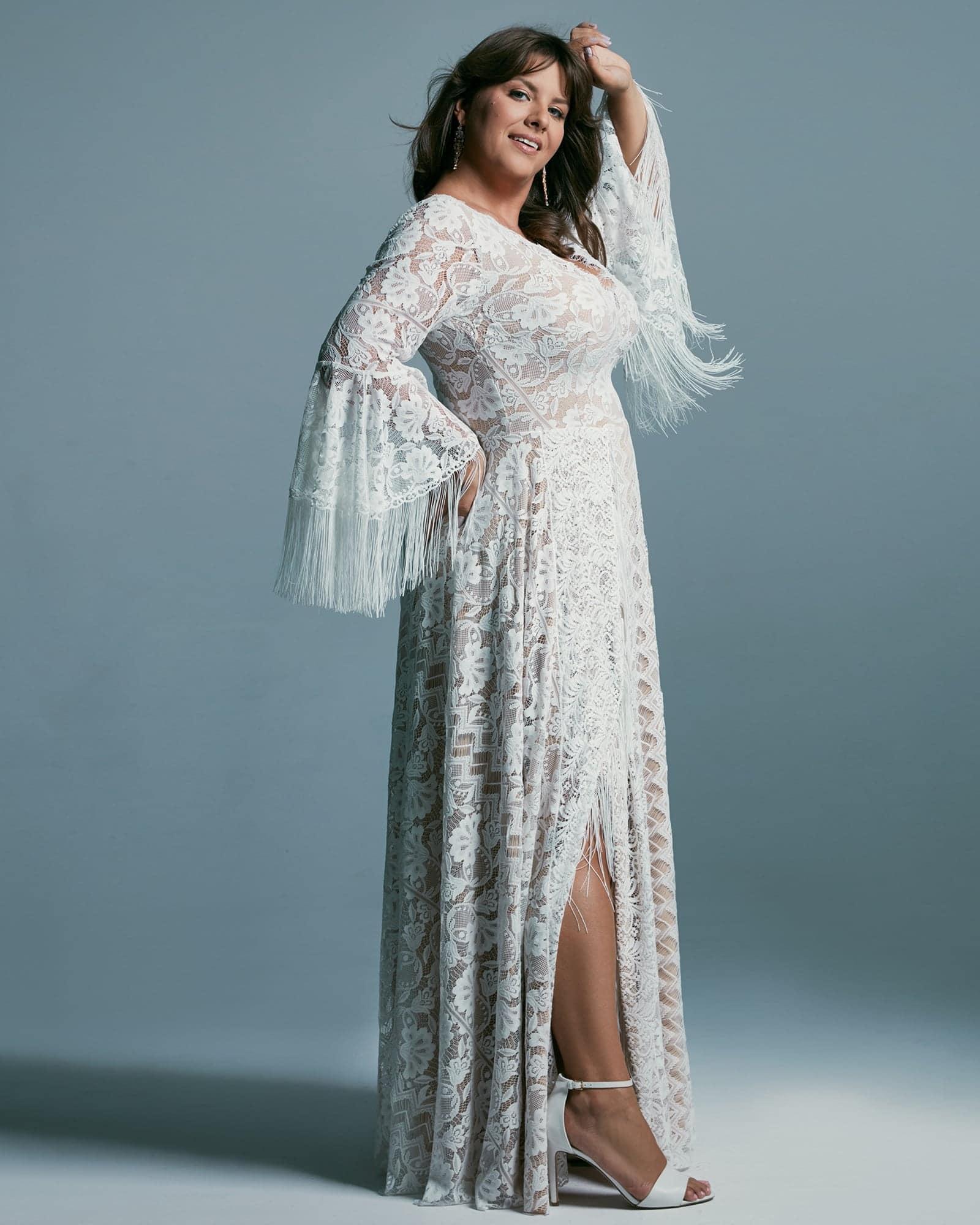 Efektowa suknia ślubna plus size z wykończonym krajką dekoltem V. Zabudowana, koronkowa z wykończonymi frędzlami długimi rękawami suknia ślubna duży rozmiar.