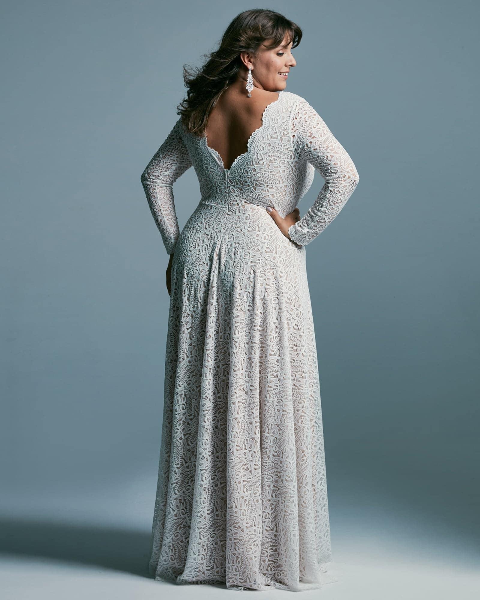 Efektowna zabudowana suknia ślubna plus size z głebokim rozcięciem na nogę. Pieknie modelująca, z długimi rękawami z koronki o delikatnej fakturze.